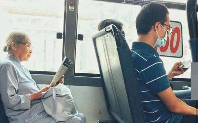 Khoảnh khắc đối lập trên chuyến bus: Một thanh thản bên tờ báo giấy, một chúi đầu vào smartphone