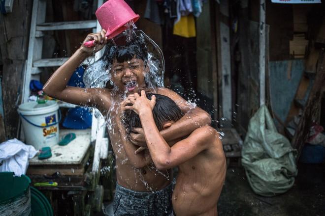 24h qua ảnh: Trẻ em tắm ngoài trời tại khu ổ chuột ở Philippines - Ảnh 3.