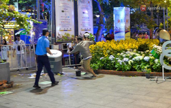 Bảo vệ ngăn cản người đàn ông mót hoa ở đường hoa Nguyễn Huệ - Ảnh 3.