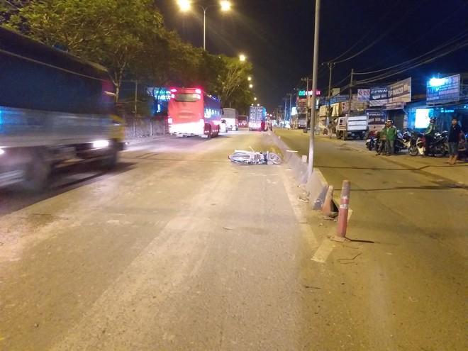 Va vào dải phân cách ngã xuống đường, người đàn ông bị xe container cán chết thương tâm - Ảnh 1.