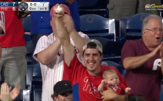 CĐV gây sốc khi vừa ôm con nhỏ vừa bắt bóng trên khán đài