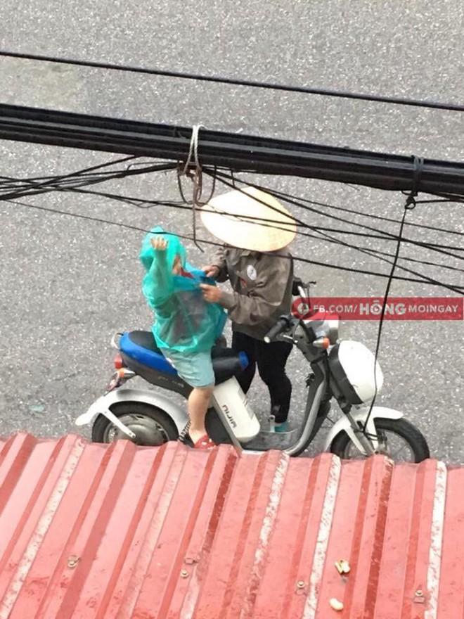 Hình ảnh người mẹ đội nón lá dừng xe giữa đường mặc áo mưa cho con trai gây xúc động - Ảnh 1.