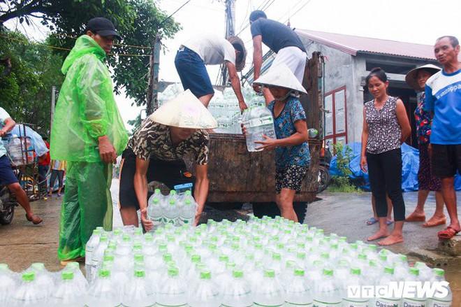 Dân vùng rốn lũ Hà Nội tấp nập chèo thuyền đi lấy nước miễn phí - Ảnh 4.