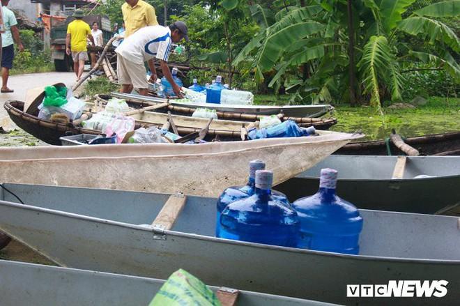 Dân vùng rốn lũ Hà Nội tấp nập chèo thuyền đi lấy nước miễn phí - Ảnh 7.
