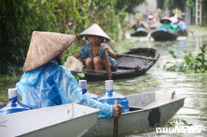 Dân vùng rốn lũ Hà Nội tấp nập chèo thuyền đi lấy nước miễn phí - Ảnh 9.