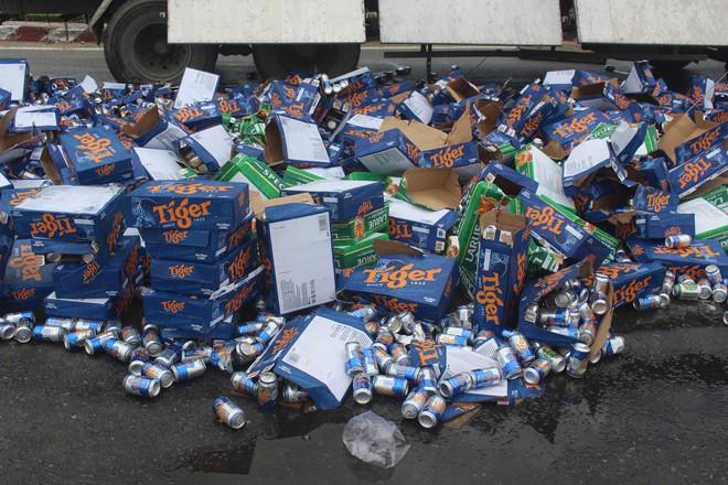 Hàng trăm thùng bia rơi xuống đường, người dân phụ tài xế thu gom - Ảnh 2.