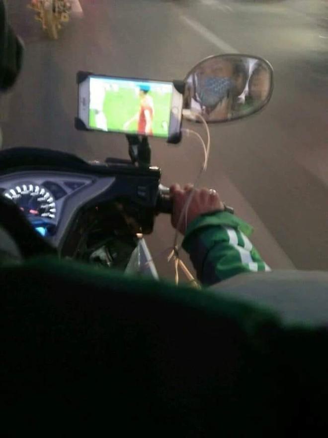 Đi đường băng băng nhưng vẫn để điện thoại xem ĐT Việt Nam, tài xế xe ôm khiến dân mạng lo lắng - Ảnh 1.