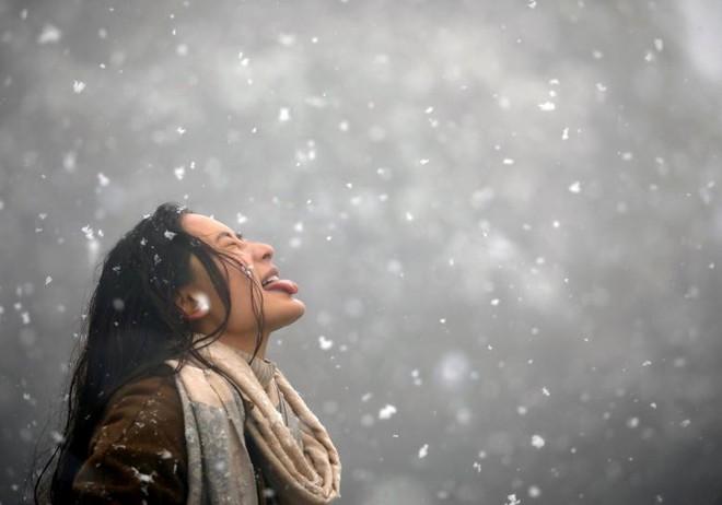 24h qua ảnh: Cô gái nếm hoa tuyết giữa trời lạnh giá - Ảnh 2.