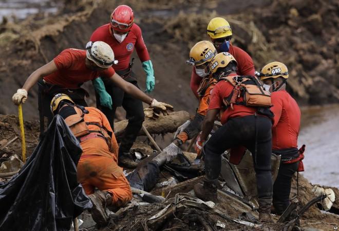 24h qua ảnh: Nhân viên cứu hộ kéo xác người trong thảm họa vỡ đập - Ảnh 2.