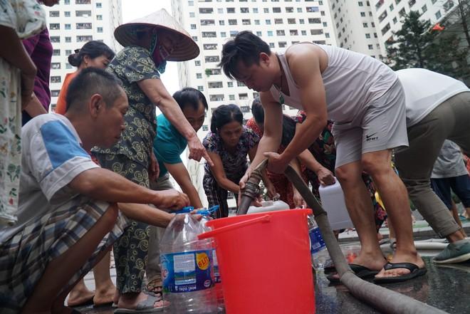 Cảnh hì hục đội mưa, hứng nước sạch xách lên tầng ở chung cư HH Linh Đàm - Ảnh 1.