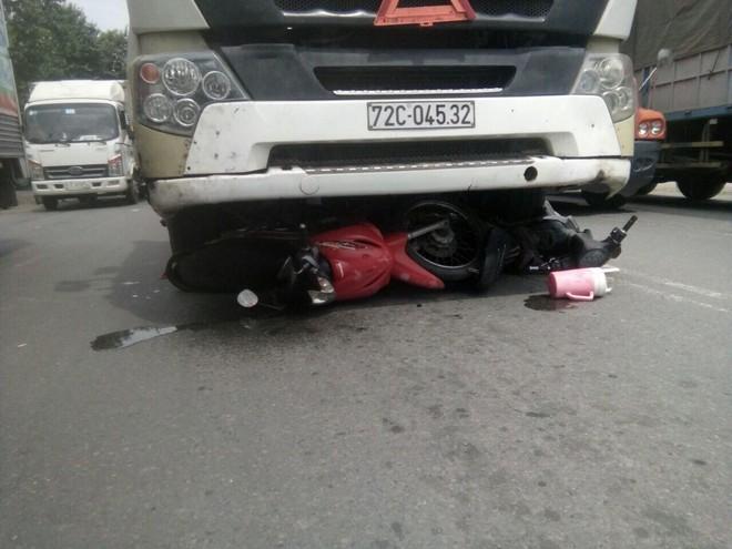 Tạt đầu xe container để qua đường, 3 người đàn ông cùng 2 xe máy bị cuốn vào gầm - Ảnh 1.