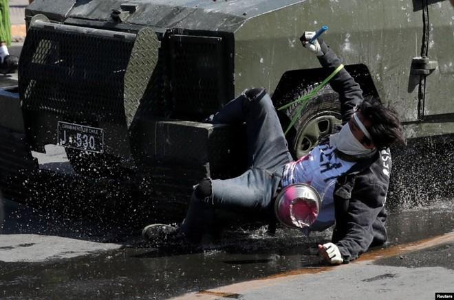 24h qua ảnh: Người biểu tình mắc kẹt trên phương tiện bọc thép cảnh sát - ảnh 3