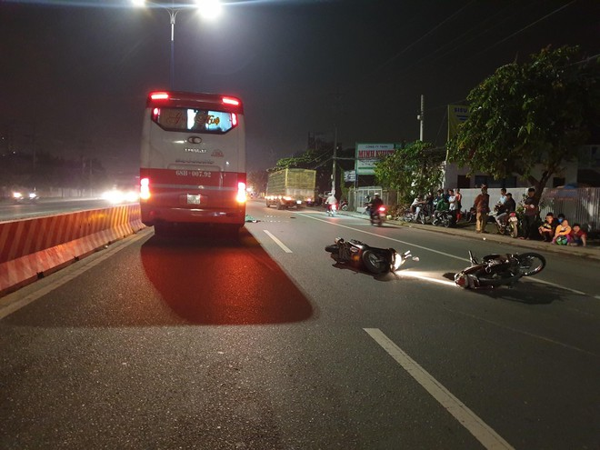 Chạy xe máy song song, 2 người bạn mắc tay lái ngã ra đường, 1 người bị xe khách cán chết - ảnh 1