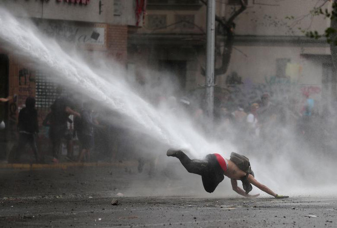 24h qua ảnh: Cảnh sát phun vòi rồng thổi bay người biểu tình - Ảnh 2.