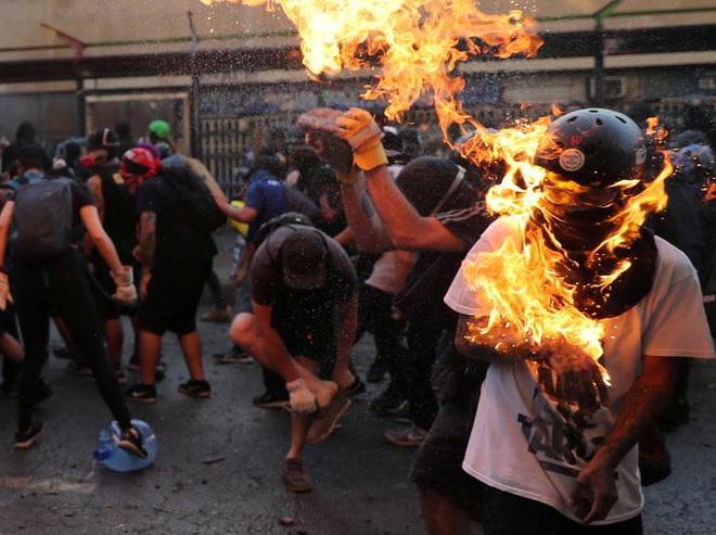 24h qua ảnh: Người biểu tình bốc cháy do trúng bom xăng ở Chile - Ảnh 2.