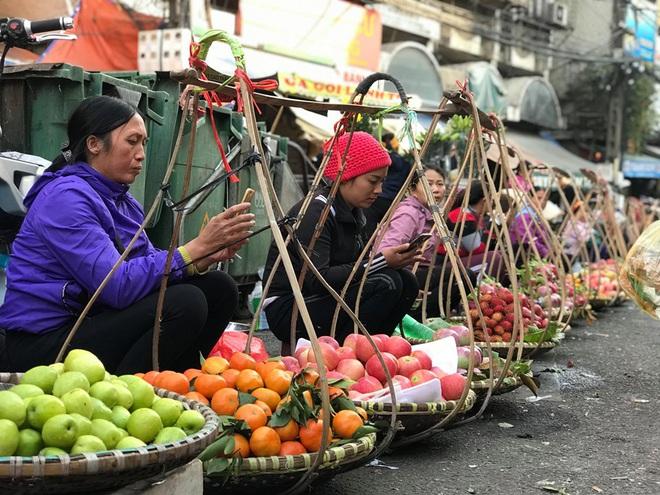 Hàng rong chợ Đồng Xuân vừa bán hàng vừa tranh thủ lên đồ cổ vũ U22 Việt Nam - Ảnh 4.