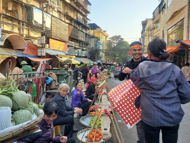 Hàng rong chợ Đồng Xuân vừa bán hàng vừa tranh thủ lên đồ cổ vũ U22 Việt Nam - Ảnh 2.