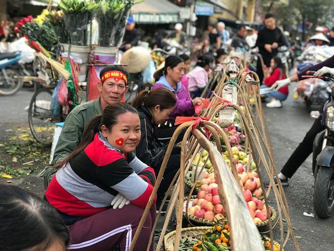 Hàng rong chợ Đồng Xuân vừa bán hàng vừa tranh thủ lên đồ cổ vũ U22 Việt Nam - Ảnh 7.
