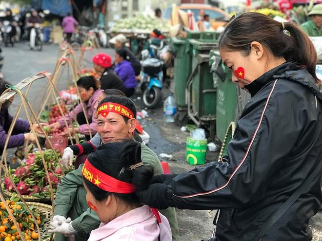 Hàng rong chợ Đồng Xuân vừa bán hàng vừa tranh thủ lên đồ cổ vũ U22 Việt Nam - Ảnh 1.