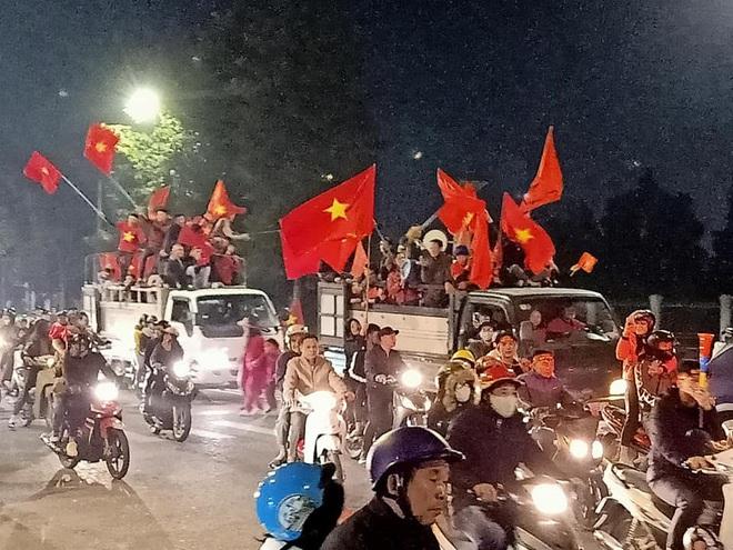 Đoàn người ngồi trên xe tải phấn khích giơ tay chào nhau, hô vang Việt Nam vô địch - Ảnh 6.