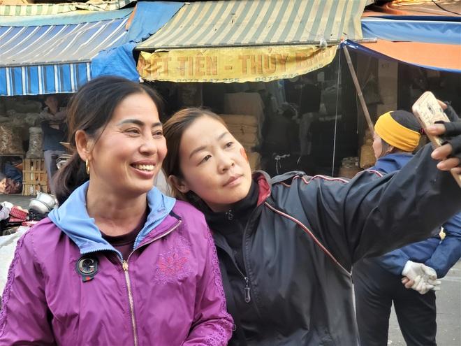 Hàng rong chợ Đồng Xuân vừa bán hàng vừa tranh thủ lên đồ cổ vũ U22 Việt Nam - Ảnh 8.