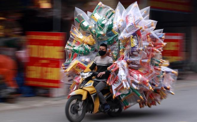 24h qua ảnh: Người đàn ông chở đầy vàng mã trên đường phố ở Việt Nam