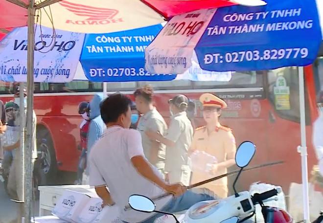 Người đàn ông cầm cây dọa đánh nữ CSGT phát nước suối miễn phí cho người đi đường - Ảnh 1.
