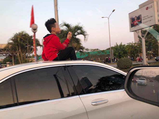 Đứa bé ngồi vắt vẻo trên nóc ô tô khiến nhiều ông bố bà mẹ sợ hãi, chỉ trích - Ảnh 1.