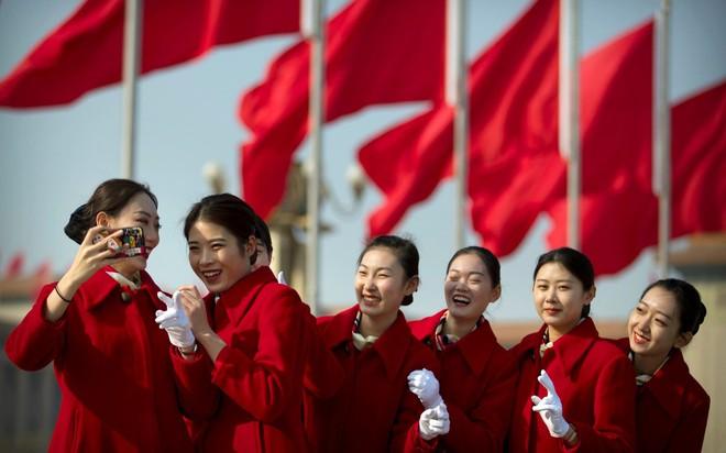 24h qua ảnh: Nhân viên lễ tân chụp ảnh trước phiên khai mạc kỳ họp quốc hội Trung Quốc - Ảnh 3.