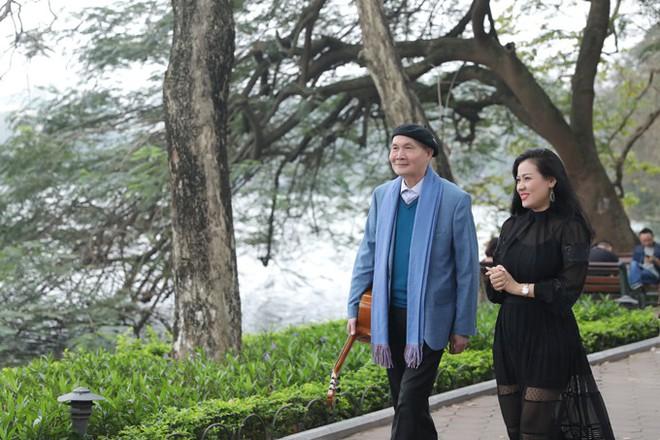 Nhạc sĩ Vũ Thành An ngẫu hứng đánh đàn guitar cho học trò hát ở Hồ Gươm - Ảnh 1.