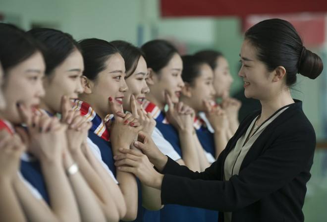 24h qua ảnh: Các nữ tình nguyện viên Trung Quốc luyện cười duyên - Ảnh 3.
