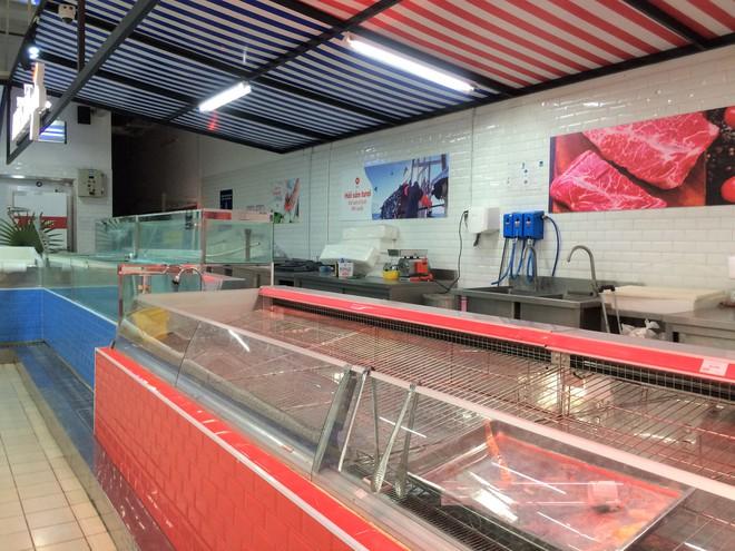 Siêu thị Auchan vắng vẻ, lặng lẽ tháo các kệ hàng sau bão giảm giá - Ảnh 3.
