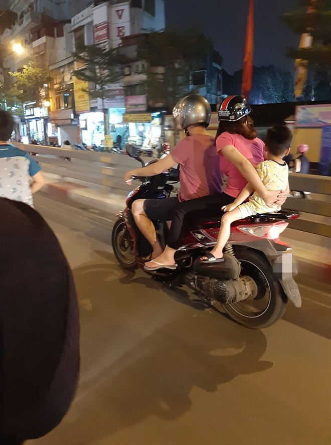 Cả gia đình di chuyển bằng xe máy trên phố Hà Nội - bức ảnh nhận nhiều dấu hỏi nhất tối Chủ nhật  - Ảnh 1.
