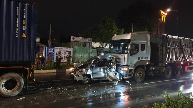 Xe 7 chỗ bẹp dúm giữa 2 xe container, người dân phá cửa cứu tài xế - Ảnh 1.