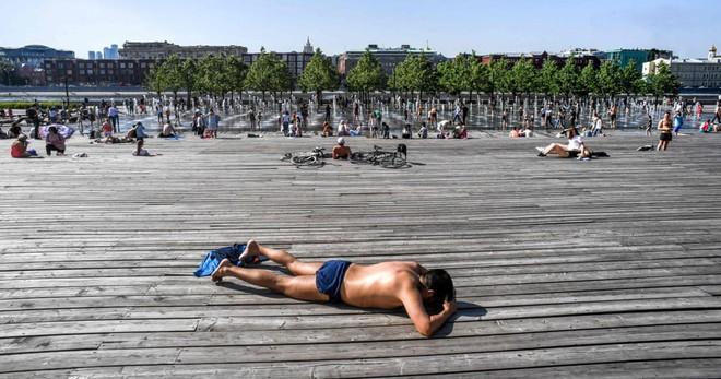 7 ngày qua ảnh: Người dân Nga tắm nắng cạnh đài phun nước ở Moscow khi nhiệt độ tăng cao - Ảnh 3.