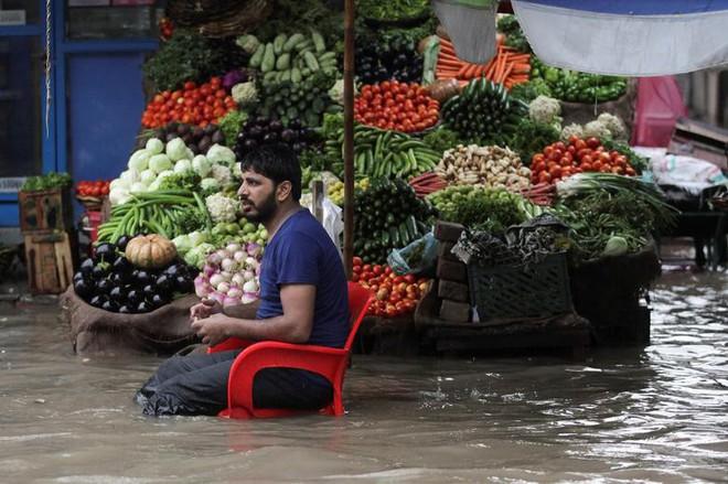 24h qua ảnh: Người đàn ông ngồi bán rau trên dòng nước đục ngầu do lụt lội - Ảnh 2.