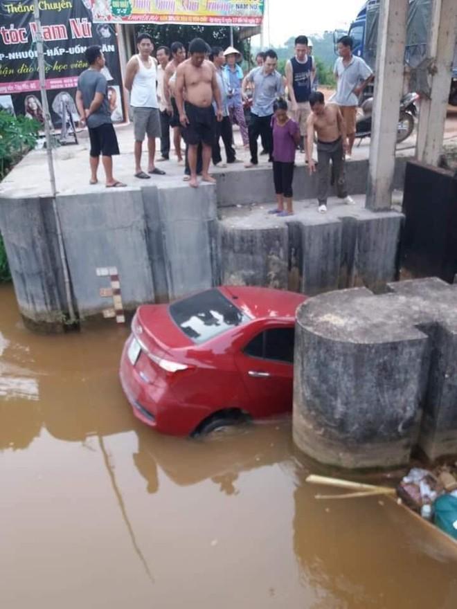 Ô tô màu đỏ nằm dưới mương, rác thải vây xung quanh khiến nhiều người tò mò - Ảnh 1.