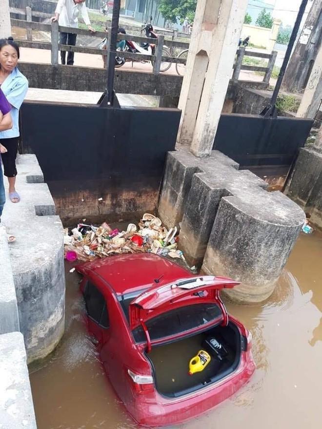 Ô tô màu đỏ nằm dưới mương, rác thải vây xung quanh khiến nhiều người tò mò - Ảnh 2.