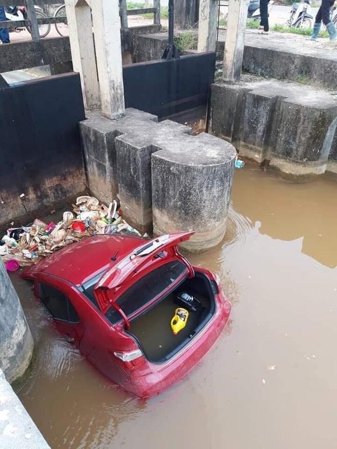 Ô tô màu đỏ nằm dưới mương, rác thải vây xung quanh khiến nhiều người tò mò - Ảnh 3.