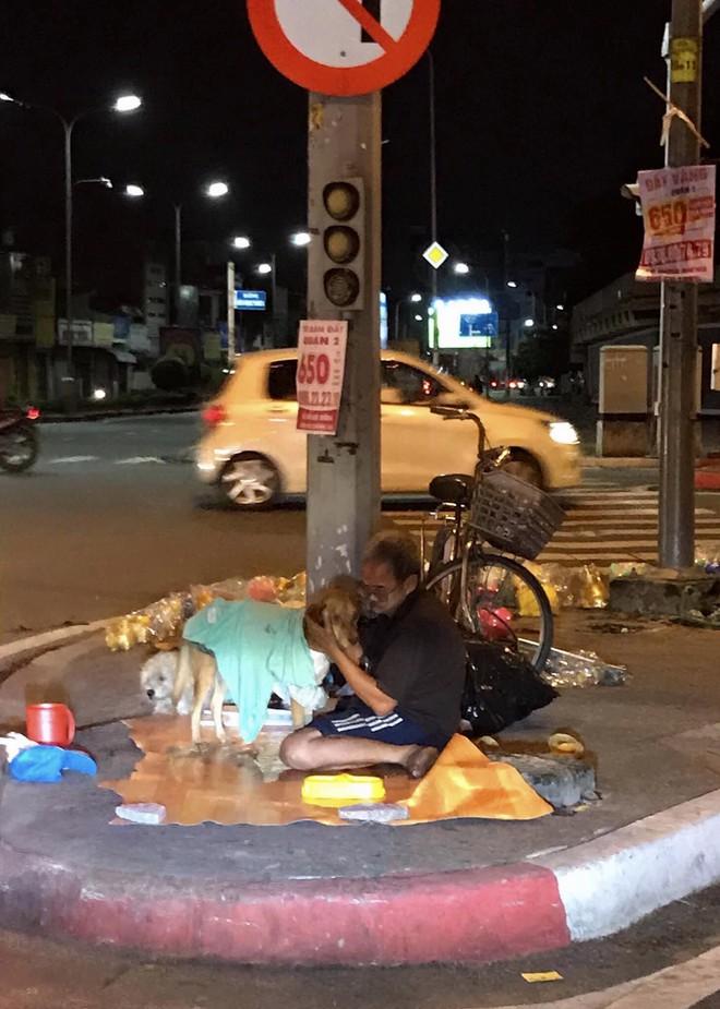 Hình ảnh cay mắt ở góc phố Sài Gòn: Cụ ông vô gia cư nhường áo, bón từng thìa thức ăn cho 2 con chó bị bỏ rơi - Ảnh 1.
