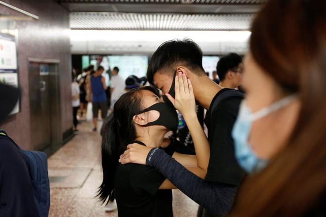 24h qua ảnh: Người biểu tình Hong Kong bịt mặt ôm hôn nhau - Ảnh 3.