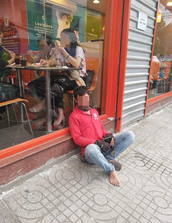 Bức ảnh thanh niên chạy xe ôm tựa vào bậc cửa quán ăn để ngồi ngủ gây tranh cãi - ảnh 1