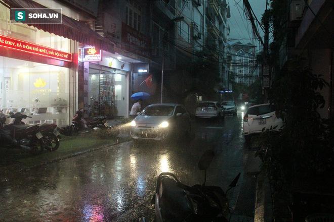 Trời Hà Nội tối đen trong cơn mưa chiều, hàng loạt xe bật đèn lưu thông - Ảnh 1.