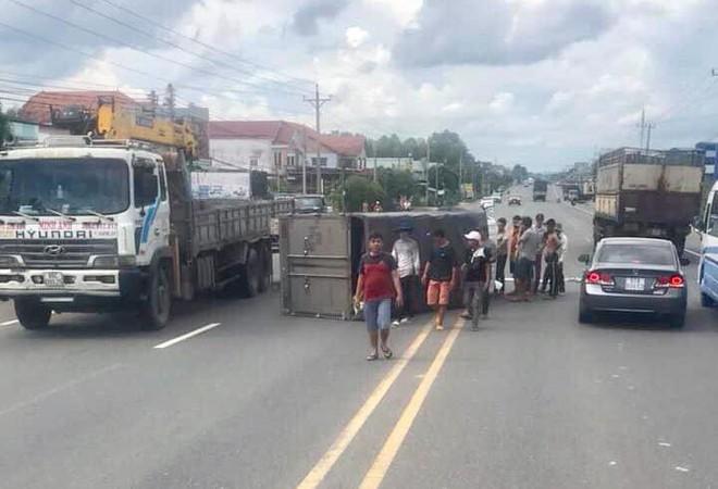 Tránh xe máy vượt ẩu khiến xe tải bị lật ngang đường, tài xế mắc kẹt trong cabin - Ảnh 1.