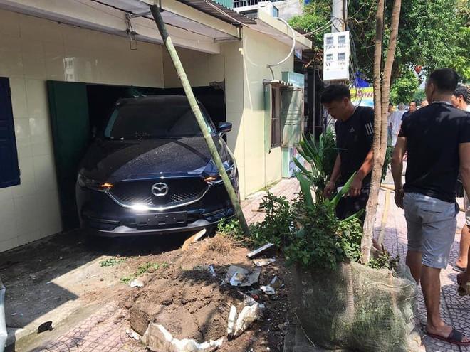 Người phụ nữ lùi ô tô mới cứng trúng nhà dân, nhóm đàn ông hốt hoảng chống cọc để tránh sập tường - ảnh 1
