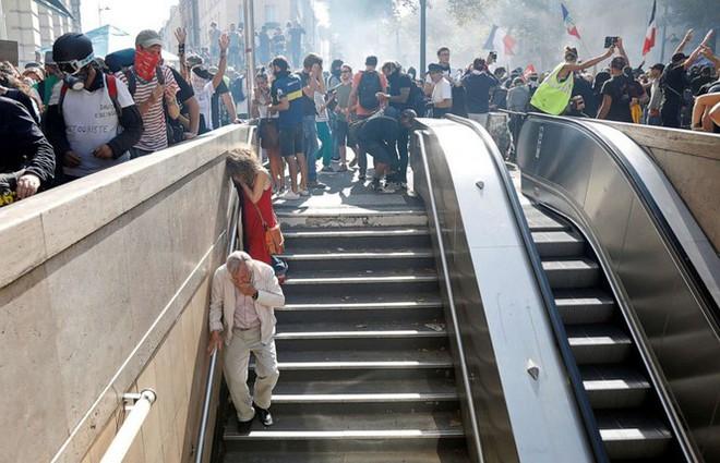 Nghệ sĩ thản nhiên chơi piano giữa lúc cảnh sát Pháp đuổi người biểu tình - Ảnh 1.