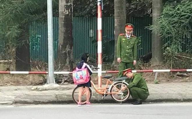 Hình ảnh 2 chú công an giúp bé gái đi học về sửa xe bị tuột xích được cộng đồng mạng chia sẻ mạnh