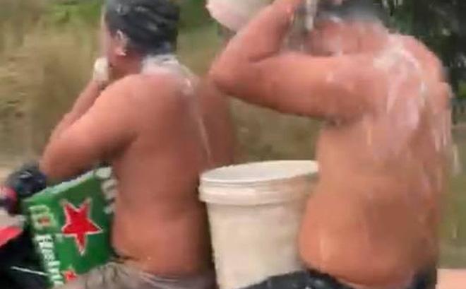 Hai thanh niên vừa chạy xe máy vừa tắm bị xử phạt 3,2 triệu đồng