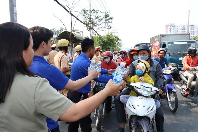 CSGT TPHCM phát nước miễn phí cho người dân lưu thông trên Quốc lộ 1 ngày 28 Tết - Ảnh 4.