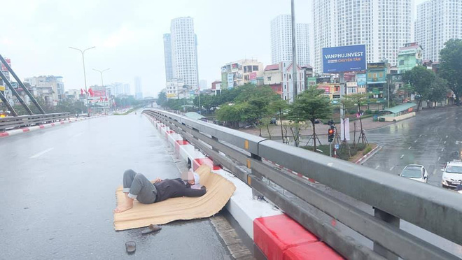 Trưa mùng 1 Tết, người đàn ông trải chiếu ra giữa phố Hà Nội để... nằm - Ảnh 1.